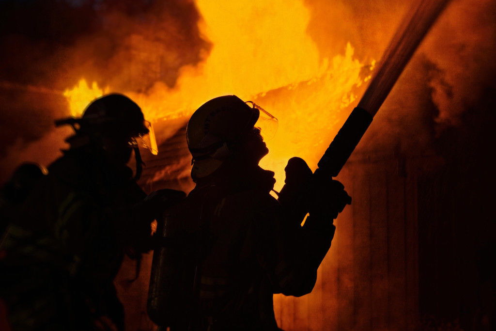 105787 firefighters using hose fighting house fire